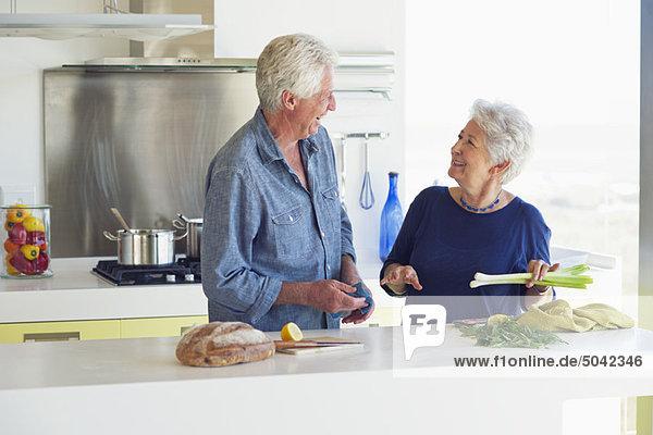 Glückliches Seniorenpaar bei der Zubereitung von Speisen in der heimischen Küche