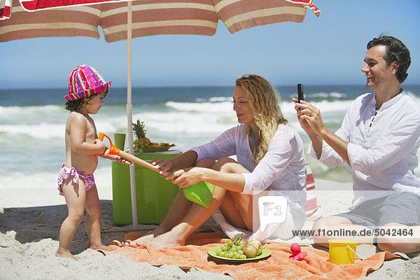 Mädchen zieht Schaufel von Mutter am Strand