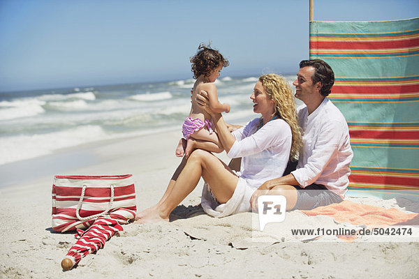 Couple playing with their daughter on the beach