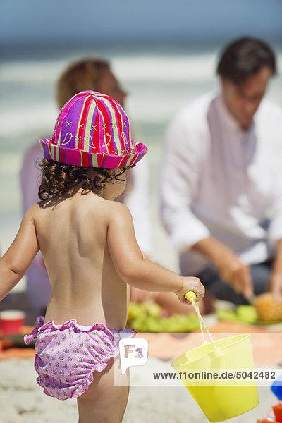 Rückansicht eines Mädchens mit einem Eimer am Strand