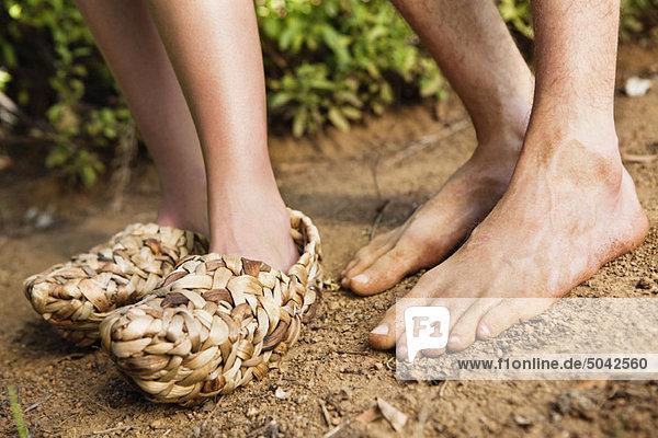 Unteransicht einer Frau mit Weidenschuhen und einem barfüßigen Mann