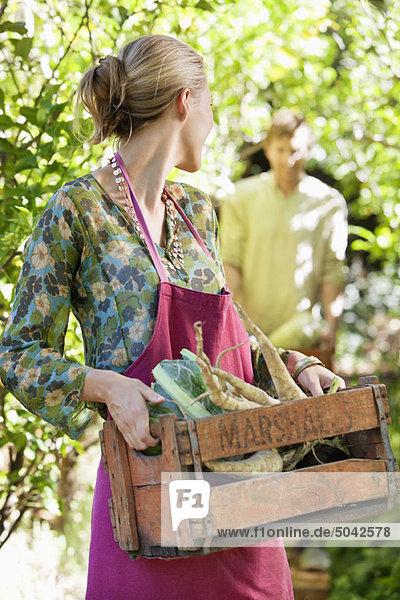 Junge Frau mit einer Kiste Rettich Junge Frau mit einer Kiste Rettich