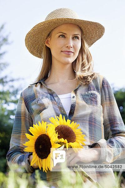 Junge Frau mit Sonnenblumen auf einem Feld