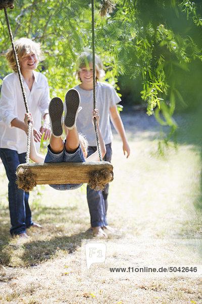 Lächelnde kleine Geschwister beim Spielen in der Baumschaukel