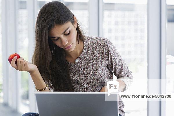 Schöne Frau  die einen Apfel hält  während sie einen Laptop benutzt.