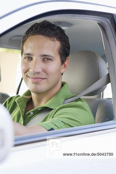 Porträt eines lächelnden mittleren Erwachsenen  der ein Auto fährt.
