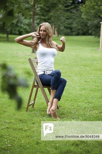 junge frau sitzt auf einem stuhl im garten mg 5168. Black Bedroom Furniture Sets. Home Design Ideas