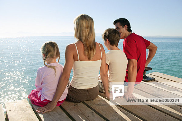 Family sitting on jetty together