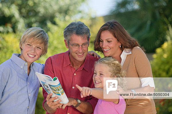 Familie beim Betrachten des Reiseführers und Zeigen