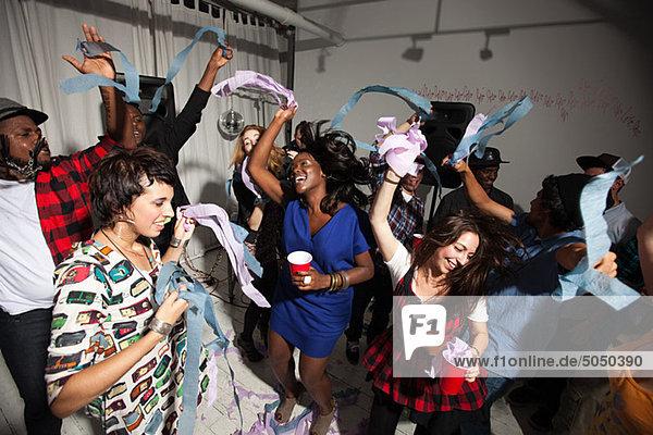 Leute  die auf einer Party mit Luftschlangen tanzen.