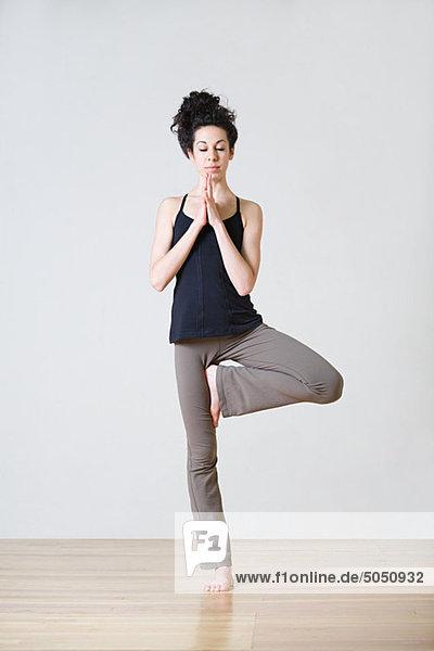 Frau im Baum Position während yoga