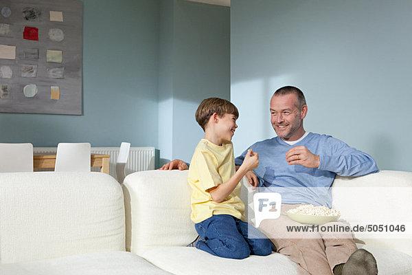 Vater und Sohn beim Fernsehen beim Popcornessen
