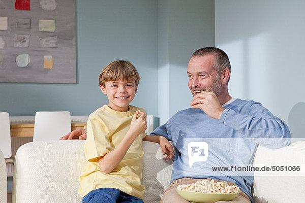 Vater und Sohn essen Popcorn