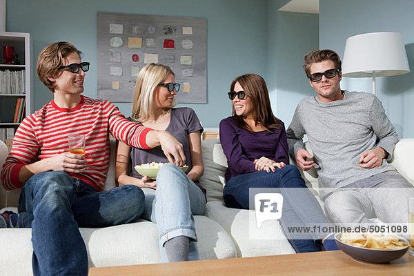 Vier Freunde sehen sich zu Hause einen 3D-Film an.