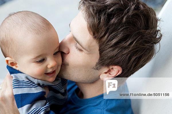 Vater küsst den kleinen Sohn auf die Wange