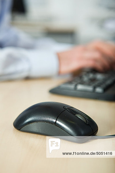Office worker using computer  mouse in foreground