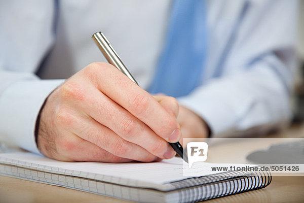 Büroangestellter in Notizbuch schreiben