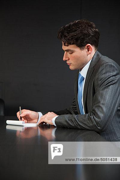 Kaufmann im Konferenzraum Notizen machen