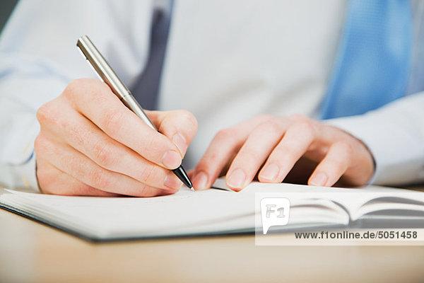 Büroangestellte schreiben im Tagebuch