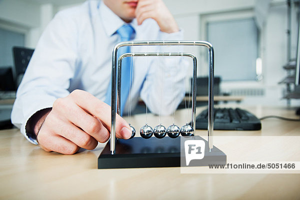 Büroangestellter spielt mit Newton-Wiege