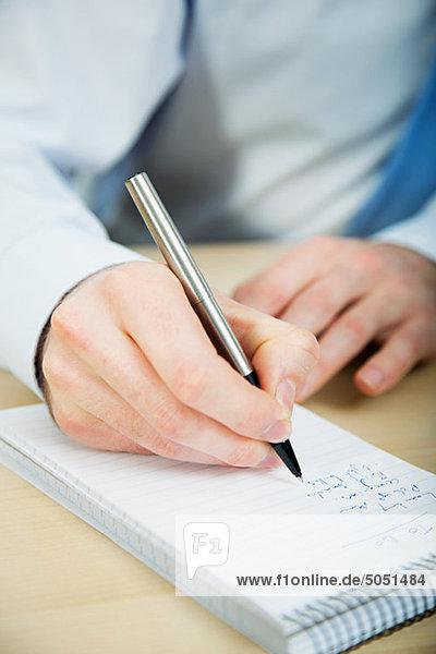 Büroangestellter schreibt in Notizbuch