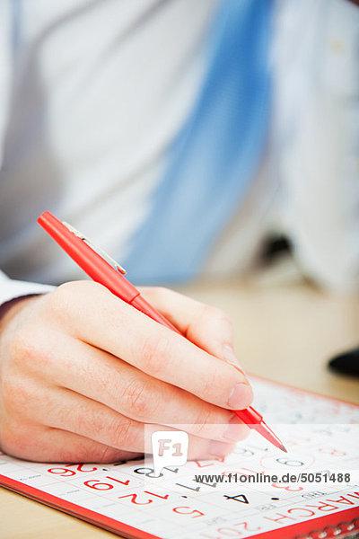 Büroberuf Kalender mit roter Stift markieren