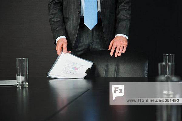 Geschäftsmann im Konferenzraum mit Unterlagen