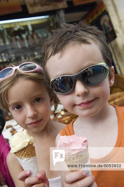 Junge Geschwister essen Eistüten Junge Geschwister essen Eistüten