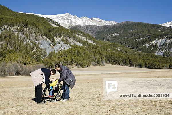 Eltern bereiten das Kind im Tragesitz vor der Wanderung vor.