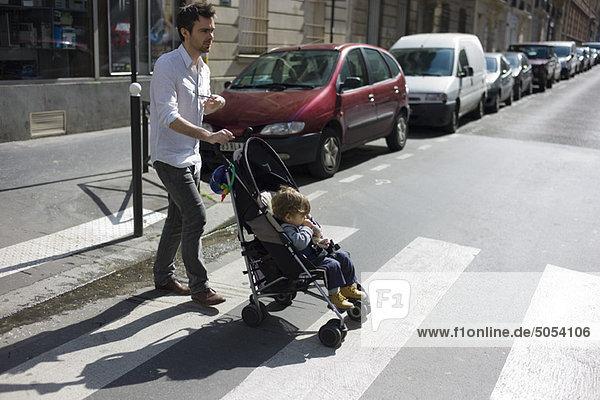 Vater schiebt Kleinkind-Sohn im Kinderwagen Vater schiebt Kleinkind-Sohn im Kinderwagen
