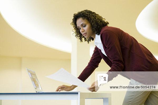 Geschäftsfrau mit Laptop-Computer und Blick auf Dokument