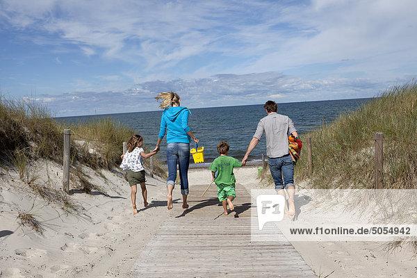 Familie läuft auf dem Strand