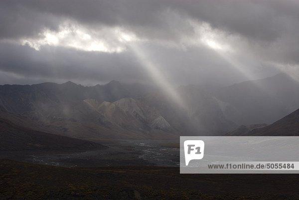 Lichtstrahlen durchscheinen Regenwolken über Polychromie Pass und Toklat River Valley. Denali-Nationalpark in Alaska  Nordamerika.