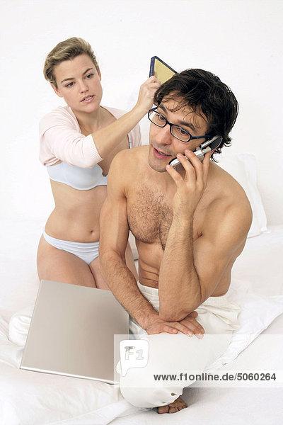 Paar sitzen auf dem Bett,  Mann unter mobile