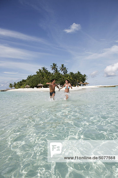 Couple at sea running in shallow water