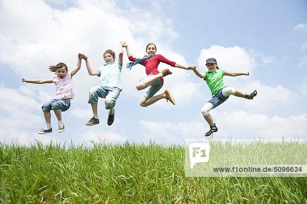 Vier Kinder springen Hand in Hand auf einer Wiese