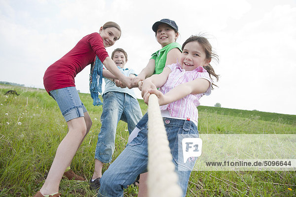 Four children playing tug-of-war