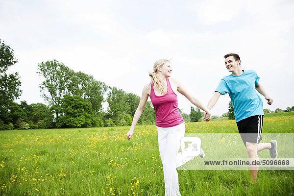 Junges Paar läuft Hand in Hand auf einer Wiese
