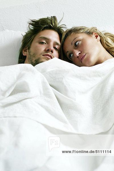 Junges Paar streitet im Bett