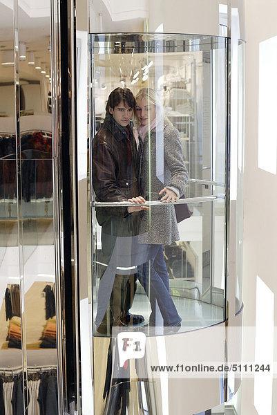 Paar in Glas Aufzug in einem Shopping-Center