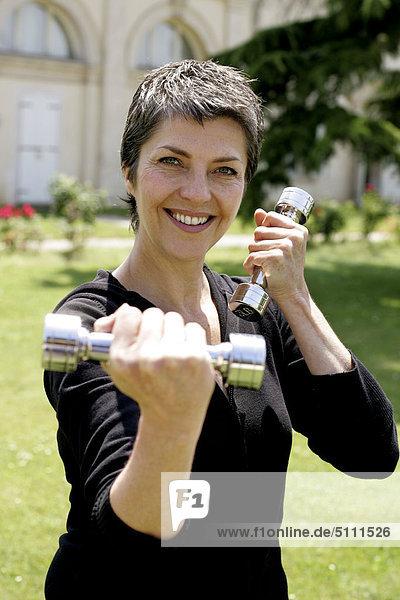 Frau beim training mit Hanteln