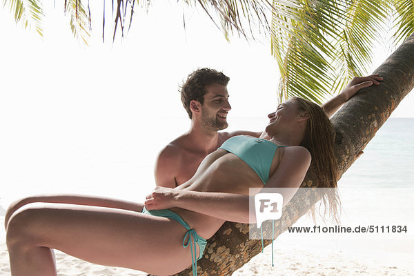 Couple talking under palm tree on beach