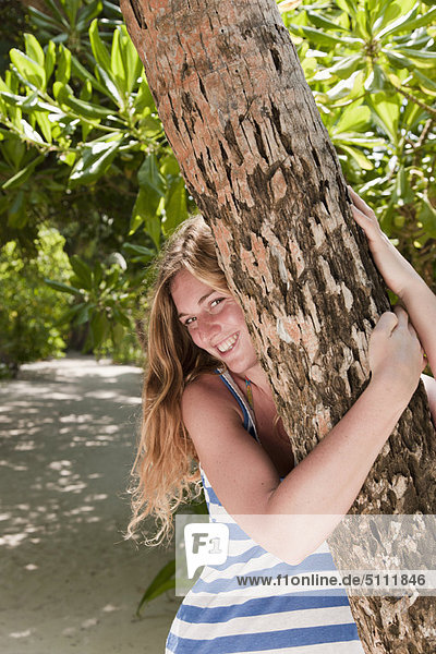 Woman hugging tree on tropical beach