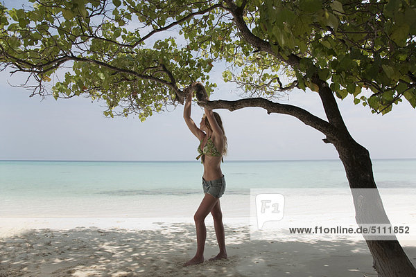 Woman standing under tree on beach