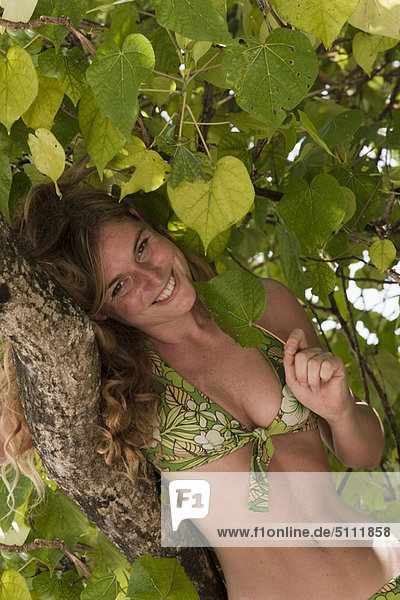 Woman sitting in tree on tropical beach