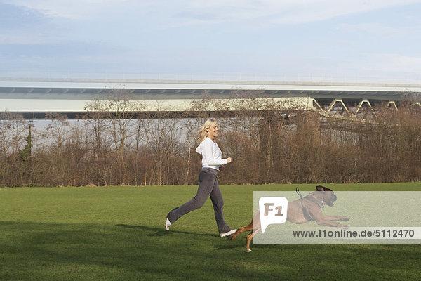Frau läuft mit Hund im Feld