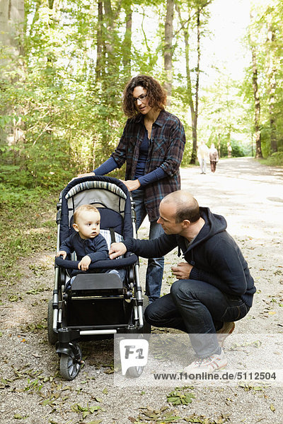 Familie schiebt Baby im Kinderwagen