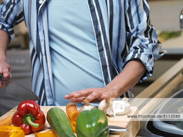 Mann hackt Gemüse in der Küche