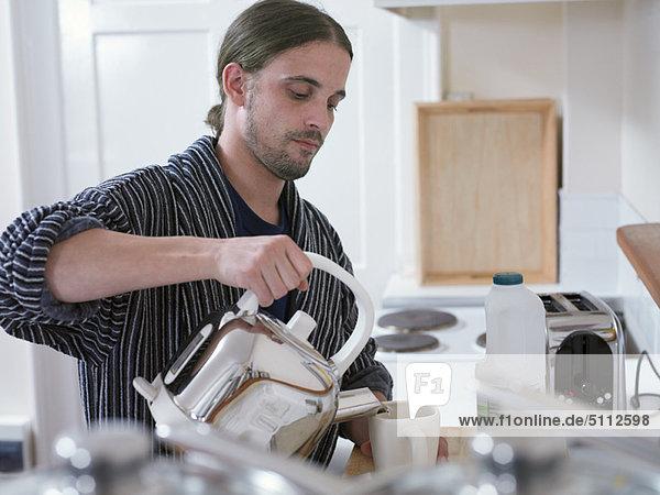 Mann macht eine Tasse Tee in der Küche