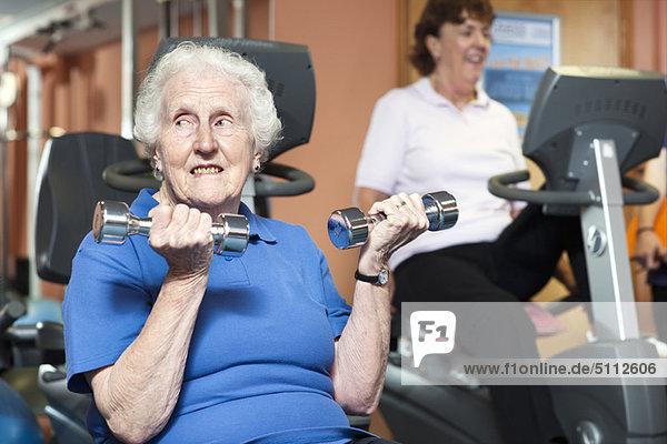 Ältere Frau beim Heben von Gewichten im Fitnessstudio